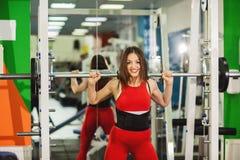 Здоровая молодая женщина со штангой, разрабатывая спортсменку работая с тяжелыми весами на спортзале стоковая фотография