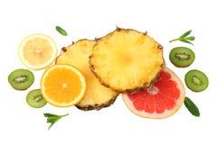 Здоровая предпосылка куски грейпфрута, плодоовощ кивиа, апельсина и ананаса изолированных на белом взгляд сверху предпосылки Стоковая Фотография