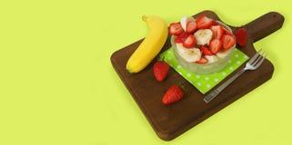 Здоровая стеклянная пластинка завтрака с прерванными клубниками и частями банана на салфетке зеленой книги на темной деревянной д Стоковые Фотографии RF