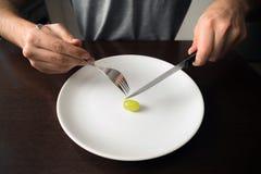 Здоровая тема еды: руки держа нож и вилку на плите с зеленой виноградиной на белой плите стоковые фотографии rf