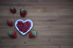 Здоровое изображение фотографии еды с свежими сочными сияющими красными семенами гранатового дерева в блюде формы сердца влюбленн Стоковые Фото