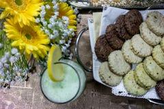 Здоровое очень вкусное домодельное питье лимонада и мяты и свежие домодельные печенья с красивыми цветками на лето стоковое изображение