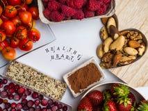 Здоровое питание для сердечно-сосудистой системы с деревянной формой сердца, семян, поленик, клубник, клюкв, вишни, гаек стоковое фото rf