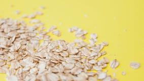 Здоровое питание, концепция Овсяная каша зерна на желтой предпосылке Хлопья овса разбросали стоковые фото