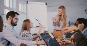Здоровое рабочее место и сыгранность Счастливая положительная бизнес-леди водя молодых многонациональных работников на обсуждении акции видеоматериалы
