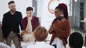 Здоровое рабочее место, счастливая усмехаясь молодая африканская бизнес-леди босса давая направления разнообразным работникам офи акции видеоматериалы