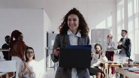 Здоровое рабочее место, счастливый кавказский женский менеджер входя в новый современный офис приветствовало с коробкой, ЭПОПЕЕЙ  акции видеоматериалы