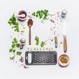 Здоровые есть и приправляя ингридиенты для вкусный варить с ложкой и ножом на белой предпосылке, взгляд сверху, рамке, положении  стоковые фото