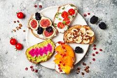 Здоровые здравицы завтрака с арахисовым маслом, бананом, granola шоколада, авокадоом, хурмой, смоквами Стоковые Фотографии RF