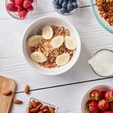 Здоровые ингридиенты завтрака на белой предпосылке woodwn Granola, гайки, ягоды, молоко, банан в шаре, взгляд сверху Стоковое фото RF