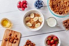 Здоровые ингридиенты завтрака с домодельными granola и ягодами на белой деревянной предпосылке Стоковая Фотография RF