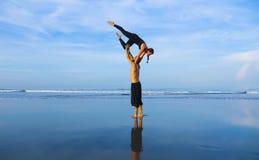 Здоровые и привлекательные подходящие пары акробатов делая баланс acroyoga и тренировку раздумья на красивый практиковать пляжа п стоковые фотографии rf