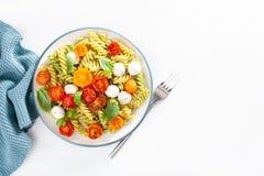 Здоровые макаронные изделия fusilli с соусом песто, зажаренными в духовке томатами, моццареллой стоковое изображение rf
