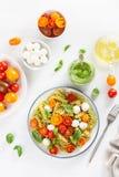 Здоровые макаронные изделия fusilli с соусом песто, зажаренными в духовке томатами, моццареллой стоковые фотографии rf