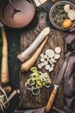 Здоровые овощи варя и есть концепцию Овощи корня лук-порея и пастернака на разделочной доске с ножом и баком с отваром Стоковые Изображения RF