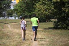 Здоровые, подходящие и sportive пары бежать в парке Стоковые Фото