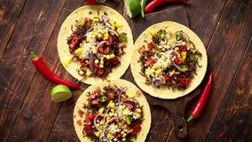 Здоровые tortillas мозоли с зажаренной говядиной, свежие горячие перцы, сыр, томаты видеоматериал