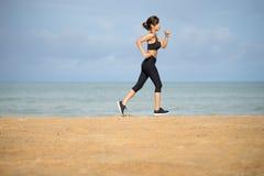 Здоровый активный образ жизни Детеныш резвится женщина фитнеса бежать на пляже на заходе солнца стоковая фотография rf
