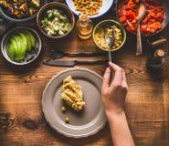 Здоровый вегетарианский салат-бар Рука женщин женская с ложкой кладет еду на плиту, взгляд сверху Чистая еда Стоковые Фото