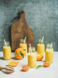 Здоровый желтый smoothie с цитрусовыми фруктами на светлой таблице Стоковые Фото