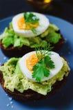 Здоровый здоровый завтрак закуски - сэндвич с авокадоом и яйцом на серой плите стоковые фото