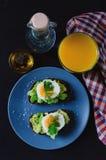 Здоровый здоровый завтрак закуски - сэндвич с авокадоом и яйцом на серой плите и стекле свежего апельсинового сока стоковые изображения rf