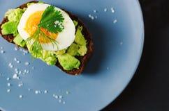 Здоровый здоровый завтрак закуски - сэндвич с авокадоом и яйцом на серой плите стоковая фотография