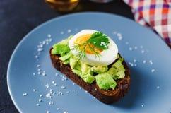 Здоровый здоровый завтрак закуски - сэндвич с авокадоом и яйцом на серой плите стоковые изображения rf