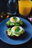Здоровый здоровый завтрак закуски - сэндвич с авокадоом и яйцом на серой плите и стекле свежего апельсинового сока стоковое фото