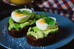 Здоровый здоровый завтрак закуски - сэндвич с авокадоом и яйцом на серой плите стоковое фото rf