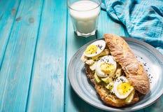 Здоровый завтрак - здравица с авокадоом, яичком и стеклом молока Стоковое Изображение RF