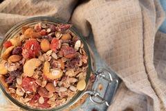 Здоровый завтрак - стеклянные опарникы овса шелушатся, granola с высушенный стоковые изображения rf