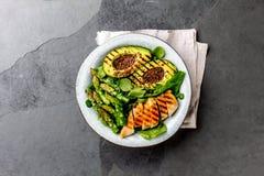 Здоровый зажаренный цыпленок, зажаренный авокадо и салат спаржи с linen семенами Сбалансированный обед в шаре серый шифер Стоковое Изображение