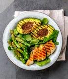 Здоровый зажаренный цыпленок, зажаренный авокадо и салат спаржи с linen семенами Сбалансированный обед в шаре серый шифер Стоковые Изображения RF