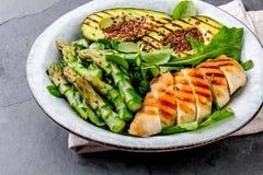 Здоровый зажаренный цыпленок, зажаренный авокадо и салат спаржи с linen семенами Сбалансированный обед в шаре серый шифер Стоковые Фотографии RF