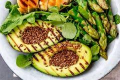 Здоровый зажаренный цыпленок, зажаренный авокадо и салат спаржи с linen семенами Сбалансированный обед в шаре серый шифер Стоковое фото RF