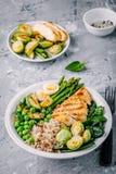 Здоровый зажаренный шар Будды овощей с цыпленком и квиноа, шпинатом, яичком, цукини, спаржей, ростками Брюсселя и зелеными гороха Стоковые Изображения
