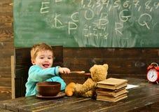 Здоровый обед в школьном кафетерии Обед доли маленького ребенка здоровый с другом игрушки Мальчик наслаждается здоровым обедом с  стоковые изображения rf