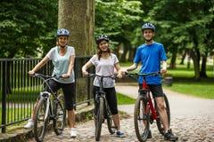 Здоровый образ жизни - велосипеды людей ехать в парке города Стоковые Изображения