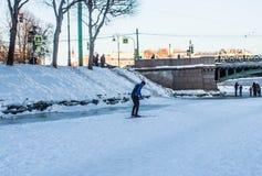 Здоровый образ жизни в городе, выходные зимы, лыжник на реке в городе Стоковые Изображения