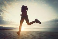 Здоровый образ жизни, женщина спорт бежать на деревянном восходе солнца променада и взморье моря стоковые фото