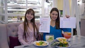 Здоровый образ жизни, красивые девушки держа калории перечисляет и план диеты усмехаясь на камере в кафе видеоматериал