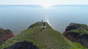 Здоровый образ жизни, пара yogi спорт делая тренировку на скале около океана, взгляд acroyoga гибкости трутня видеоматериал