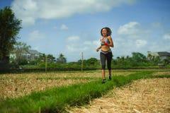 Здоровый портрет образа жизни молодой счастливой и подходящей юговосточной азиатской тайской женщины бегуна в идущей разминке out стоковые изображения