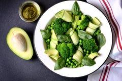 Здоровый салат брокколи, зеленых горохов, огурца и авокадоа с базиликом и оливковым маслом еда здоровая Взгляд сверху, космос экз Стоковое фото RF