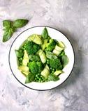 Здоровый салат брокколи, зеленых горохов, огурца и авокадоа с базиликом и оливковым маслом еда здоровая Взгляд сверху, космос экз Стоковое Изображение