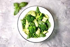 Здоровый салат брокколи, зеленых горохов, огурца и авокадоа с базиликом и оливковым маслом еда здоровая Взгляд сверху, космос экз Стоковые Фото