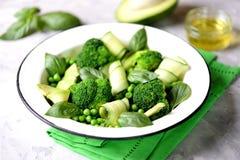 Здоровый салат брокколи, зеленых горохов, огурца и авокадоа с базиликом и оливковым маслом еда здоровая Взгляд сверху, космос экз Стоковое Изображение RF