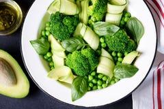 Здоровый салат брокколи, зеленых горохов, огурца и авокадоа с базиликом и оливковым маслом еда здоровая Взгляд сверху, космос экз Стоковая Фотография