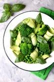 Здоровый салат брокколи, зеленых горохов, огурца и авокадоа с базиликом и оливковым маслом еда здоровая Взгляд сверху, космос экз Стоковые Изображения